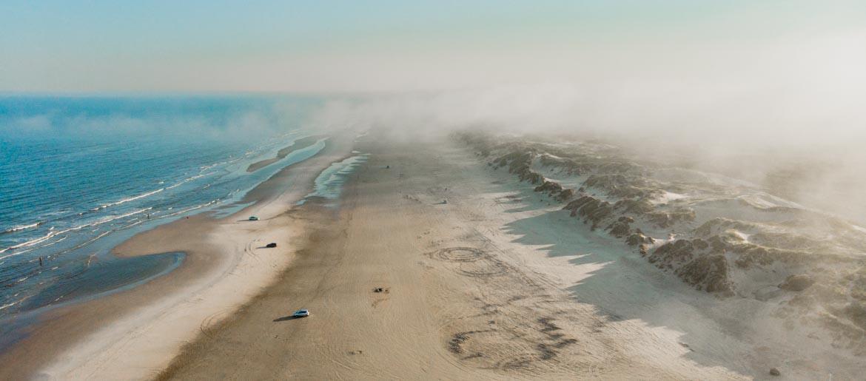 widok na plażę z mgłami z drona